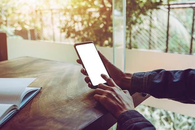 Mobile écran blanc dans les mains du jeune homme dans un café
