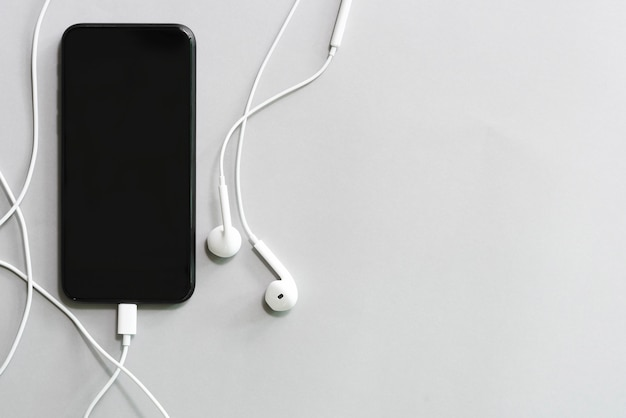 Mobile avec écran noir et écouteurs sur tableau blanc avec espace de copie gratuit.