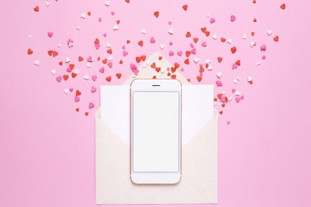 Mobile avec enveloppe et coeurs rouges sur rose