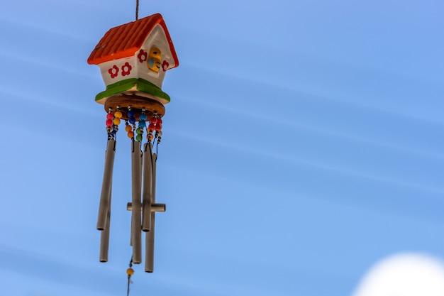 Mobile de petite maison en plein air suspendu avec une clochette devant la maison avec un ciel flou