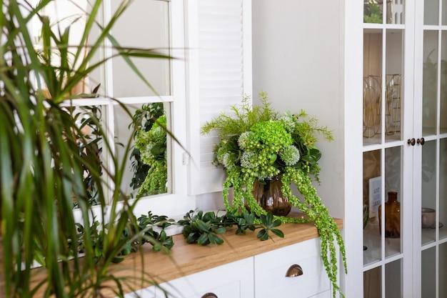 Mobilier moderne blanc, partie du salon lumineux et confortable. appartements élégants, plantes vertes.