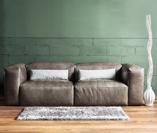 Mobilier et mur en béton avec éclairage ponctuel, faible profondeur de champ, mise au point sur un canapé marron.