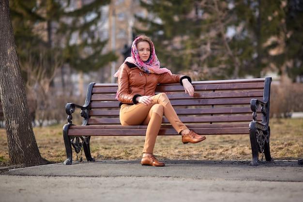 Mocassins bruns sur les pieds d'une belle jeune femme qui est assise sur un banc dans le parc avec un mouchoir sur la tête et sourit