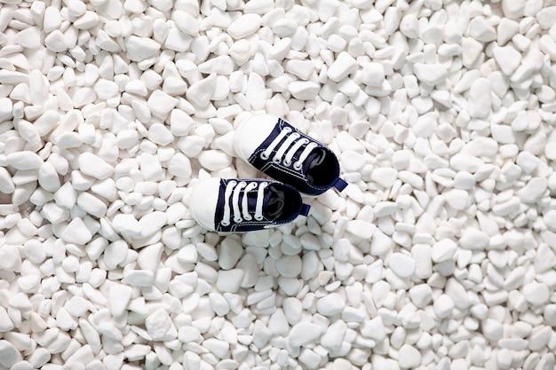 Mocassins pour enfants sur des pierres de la mer blanche