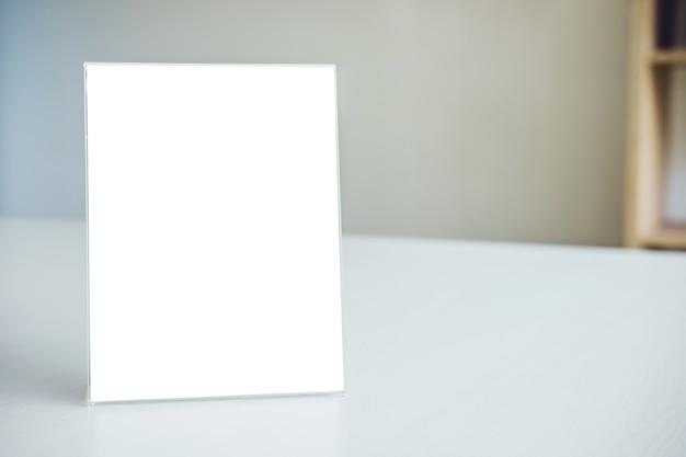 Mock up cadre de menu blanc sur table dans un poste de travail moderne pour votre texte
