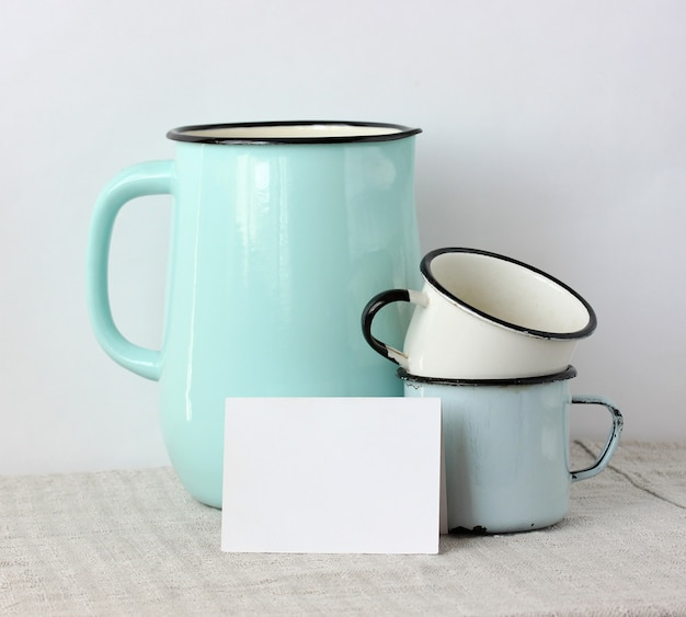 Mockup, créateur de scène. plats en émail et une carte vierge blanche sur la table. le pichet et les tasses. copie espace.