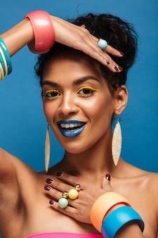 Mode afro américaine femme verticale avec des cosmétiques colorés montrant les mains avec des accessoires sur l'appareil photo isolé, sur le mur bleu