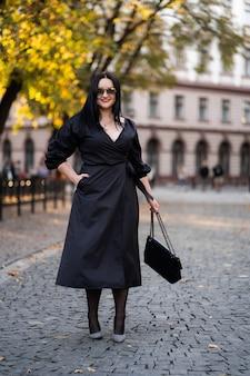 Mode d'automne. la fille aux lèvres rouges dans une robe noire élégante à la mode et des lunettes de soleil, style de vie automnal sur le fond des arbres verts jaunes flous dans le parc.