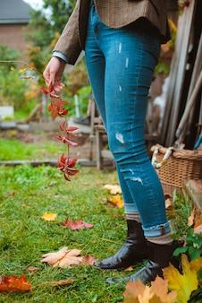 Mode d'automne. une jeune femme hipster dans une veste chaude marron et un jean. décor d'automne avec des couronnes et des citrouilles.