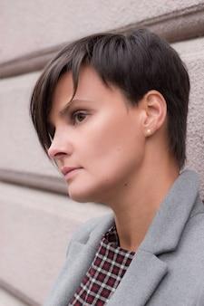 Mode d'automne. la jeune fille brune aux cheveux courts en manteau gris élégant à la mode et lunettes de soleil, posant sur le fond du bâtiment. mode de rue.