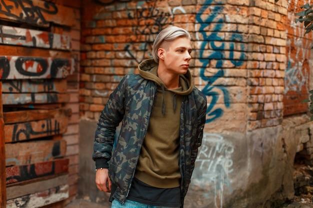 Mode beau modèle masculin en veste militaire près du mur