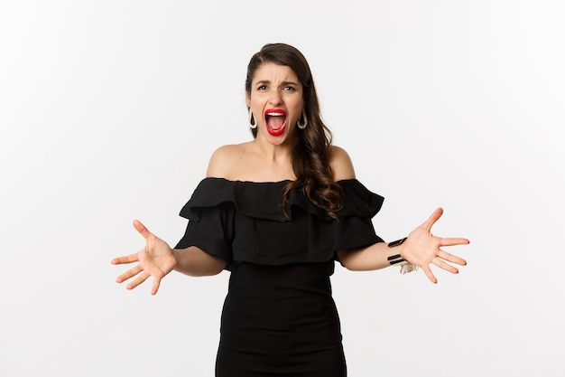 Mode et beauté. femme en colère en robe noire, criant des mains folles et se serrant la main, grimaçant outrée à la caméra, debout sur fond blanc.