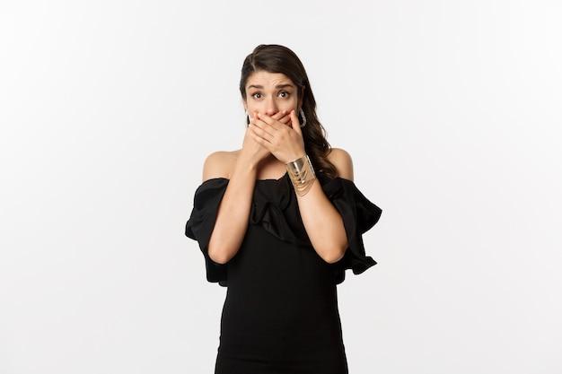 Mode et beauté. femme en robe noire couvrir la bouche et haletant choqué, regardant la caméra inquiète, debout sur fond blanc.