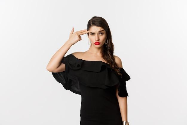 Mode et beauté. jeune femme agacée en robe noire faisant un geste de pistolet près de la tête, se tirant d'irritation, debout sur fond blanc.