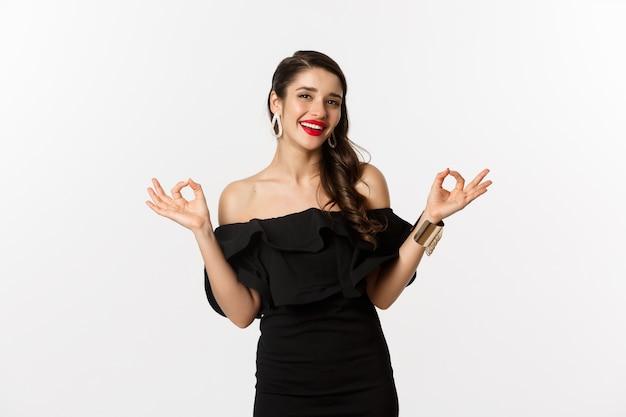 Mode et beauté. jolie femme brune en robe noire, montrant des signes corrects et souriant satisfait, approuve et recommande, debout sur fond blanc.