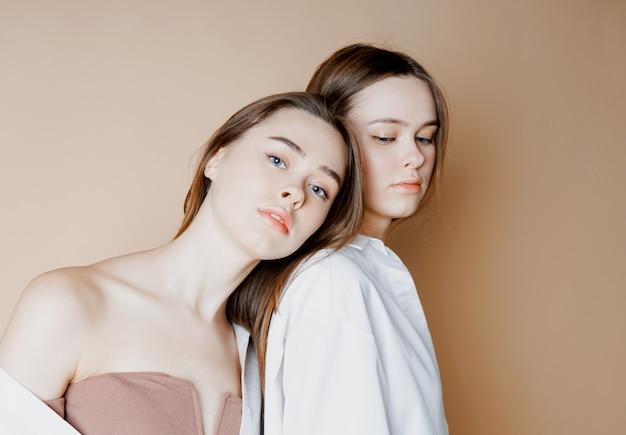 Mode beauté modèles deux soeurs jumelles belles filles nues en regardant la caméra isolée sur fond beige