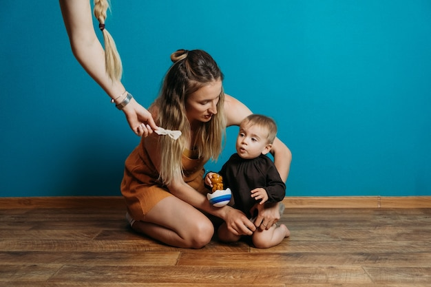 Mode bébé choisir robe et accessoires maman habille le petit bébé fille à la maison mère