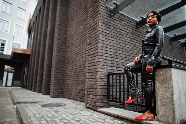 Mode belle femme afro-américaine posant en veste en cuir noir et pantalon à la rue.