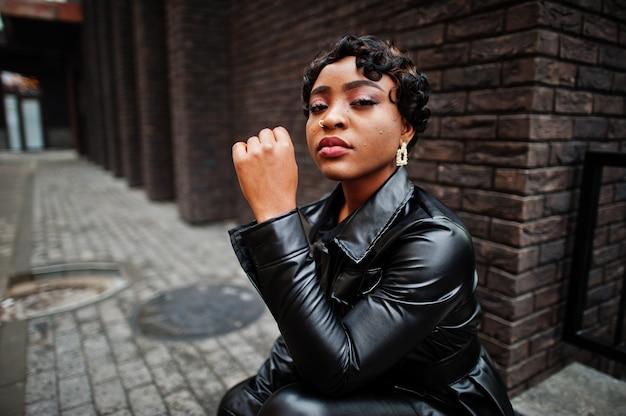 Mode belle femme afro-américaine posant en veste en cuir noir à la rue. boucle d'oreille dans le nez.