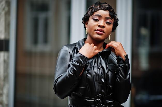 Mode belle femme afro-américaine posant en veste en cuir noir à la rue.