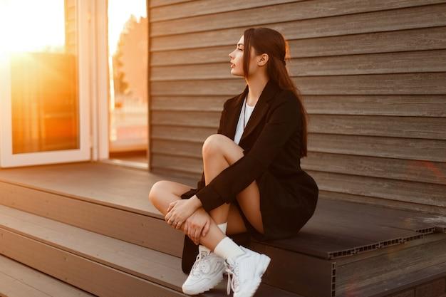 Mode belle femme modèle élégant en manteau vogue noir avec des chaussures blanches