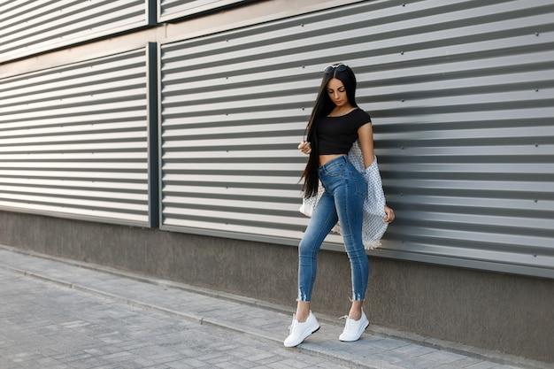 À la mode belle jeune femme aux longs cheveux noirs dans une cape élégante blanche