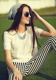 Mode élégante belle jeune femme brune modèle en été vêtements décontractés hipster posant sur fond de rue dans le parc