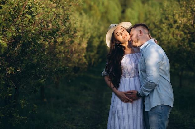 À la mode et élégante femme enceinte heureuse et son mari habillé d'un ton pastel blanc et bleu dans le jardin au coucher du soleil