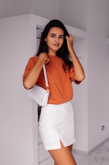 Mode élégante jeune femme de race blanche blogueuse à la maison dans la chambre à coucher portant une chemise et une jupe de couleur brique
