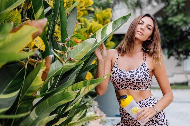 Mode élégante jeune femme sportive caucasienne fit en haut camisole léopard et short de motard à l'extérieur détient un shaker de protéines