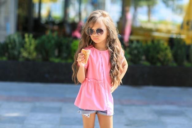Mode enfant été dans la ville se dresse sur un streetl. fille branchée à lunettes de soleil debout dans la rue au coucher du soleil.