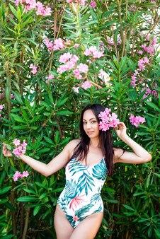 Mode d'été. femme en maillot de bain près des feuilles de palmier vert à la nature tropicale. belle fille avec un corps en forme à la mode avec des fleurs dans les cheveux dans la jungle.