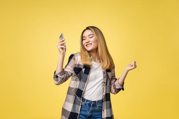 Mode femme asiatique souriante, écouter de la musique dans les écouteurs sur fond jaune.