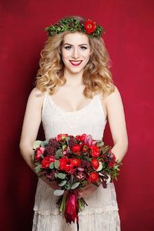 Mode femme aux cheveux blonds bouclés. mariée avec des fleurs