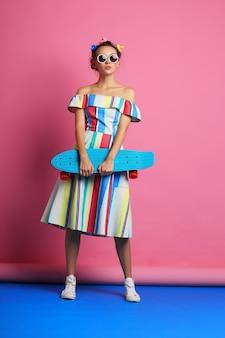 Mode femme cool posant avec planche à roulettes. femme jeune hipster avec bigoudis dans ses cheveux, lunettes de soleil, baskets blanches. tourné en studio