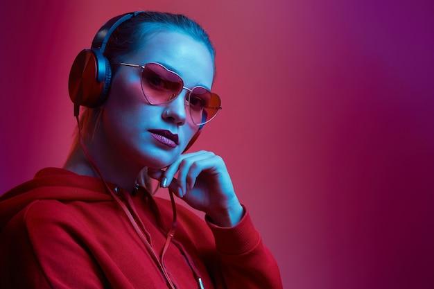 Mode femme hipster porter des lunettes et des écouteurs élégants en écoutant de la musique sur un mur de néon de couleur