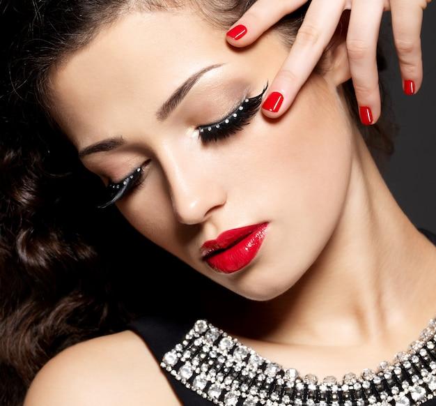 Mode femme avec maquillage créatif moderne à l'aide de faux cils manucure rouge