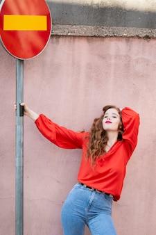 Mode femme posant à côté du panneau de signalisation