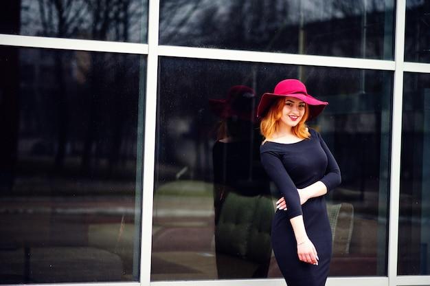 Mode fille aux cheveux rouge sur un chapeau rose et une robe noire avec lumineux font sur une grande fenêtre