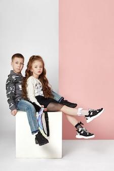 Mode garçon et fille vêtements élégants mur coloré