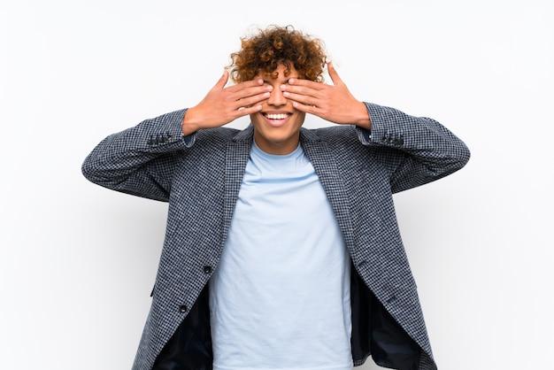 Mode homme afro-américain sur mur blanc isolé, couvrant les yeux par les mains