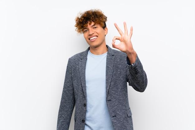 Mode homme afro-américain sur mur blanc isolé, montrant un signe ok avec les doigts