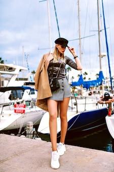 Mode image pleine longueur de femme posant dans la rue près de la marina avec des yachts, tenue à la mode glamour moderne, vacances luxueuses, printemps automne. modèle sexy posant dans la rue.