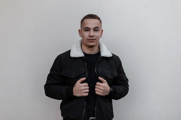 Mode jeune bel homme en vêtements noirs élégants se tient près du mur gris