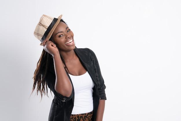 À la mode jeune belle femme africaine avec qui pose en veste en cuir noir.