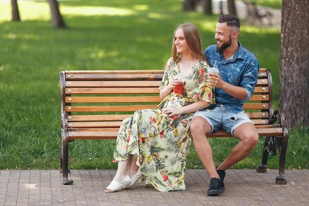 Mode jeune couple d'adolescents au repos dans un parc de la ville avec des boissons assis sur un banc sur une journée d'été ensoleillée