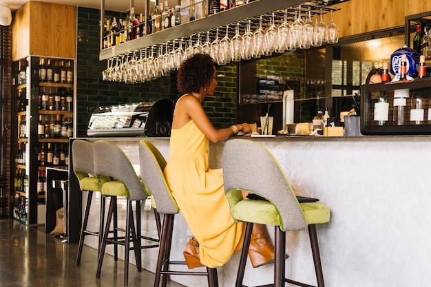À la mode jeune femme assise avec cocktail au comptoir