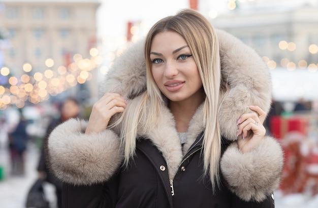 Mode jeune femme blonde en manteau de mode dans la ville.