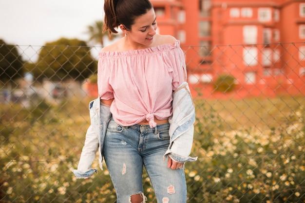 La mode jeune femme debout devant la clôture à la recherche de suite