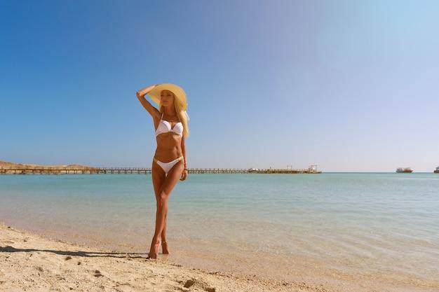 Mode jeune femme debout près de l'eau sur la plage